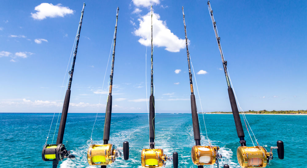 A line of rods in the water on a fishing boat